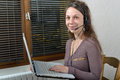 Helpline female customer support operator with headset and smiling Stock Photo