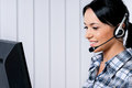 Helpline operator smiling female with headphones giving a consultation Stock Photography