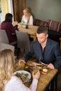 Hembra de eating food with del hombre de negocios Foto de archivo libre de regalías