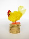 Hen laying golden eggs little toy standing on pile of coins Stock Image