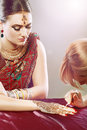 Henna being applied a female artist applies a design to the back of a woman s hands Stock Images