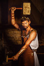 Hephaestus smith blacksmith in a leather apron in a forgery with the hammer and anvil Royalty Free Stock Photos