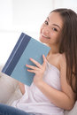 It is her favourite book beautiful young cheerful woman holding a and smiling Royalty Free Stock Images