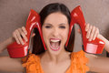 Her favourite shoes excited young woman holding red heeled near face and shouting Royalty Free Stock Image