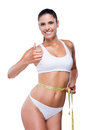 Her personal achievement attractive young woman in white bra and panties showing thumb up while measuring body with tape and Stock Photos