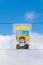 Heraldic banner in middleburg zeeland showing a knight over a shield and crown suspended between two wires against a cloudy blue Royalty Free Stock Photography