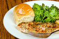 Herb crusted baked chicken breast with kale and buttered roll Royalty Free Stock Photography