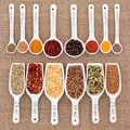 Herb and spice measurement selection in metric measuring spoons scoops over hessian Royalty Free Stock Photo