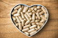 Herbal drug capsules a heart shaped box wooden surface alternative medicine concept Royalty Free Stock Image