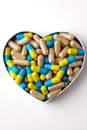Herbal drug capsules a heart shaped box wooden surface alternative medicine concept Royalty Free Stock Photography