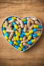 Herbal drug capsules a heart shaped box wooden surface alternative medicine concept Stock Images