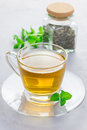 Herbal mint tea in glass cup with dry peppermint tea on background, vertical Royalty Free Stock Photo