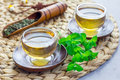 Herbal mint tea in oriental glass cup with fresh peppermint and tea scoop on background, horizontal Royalty Free Stock Photo