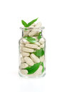 Herbal supplement pills and fresh leaves in glass