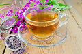 Herbal tea from fireweed in a glass cup with strainer metal dry flowers fresh flowers of on the background of wooden boards Stock Image