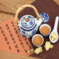 Herbal tea ginger used in chinese medicine with mandarin calligraphy on rice paper and teapot sheng jiang translation describes Stock Images
