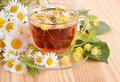 Herbal tea with linden and camomile flowers on a wood table background Royalty Free Stock Photography