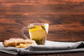 Herbal tea. Sweet lemon tea and a cut ginger on a wooden background. A cup of ginger tea. Natural and hot drinks for breakfast. Royalty Free Stock Photo