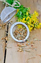Herbal tea from tutsan dry and fresh in a strainer metal with flowers flowers against wooden board Stock Photos