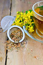 Herbal tea from tutsan dry in strainer with cup metal flowers fresh flowers of hypericum a glass on a wooden boards background Royalty Free Stock Image