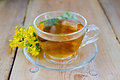 Herbal tea from tutsan in a glass cup on a board fresh flowers against wooden Stock Photo