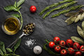Herbs mix with tomatoes and olive oil on the black stone table green basil rosemary bay leaf salt capers garlic Royalty Free Stock Photos