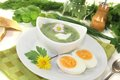 Herbs soup with eggs a dollop of cream green and daisy Royalty Free Stock Images
