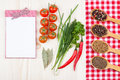 Herbs and spices a blank notepad beside fresh tomatoes aromatic dried on a red checked tablecloth Royalty Free Stock Photography