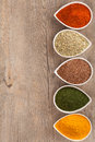 Herbs and spices border colourful ground or dried with copy space on the side includes turmeric cayenne pepper dill flax seed Stock Photography