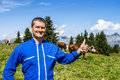 Herdsman and cows standing in front of in alpine mountains Stock Photo