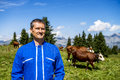 Herdsman and cows standing in front of in alpine mountains Royalty Free Stock Image
