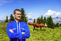 Herdsman and cows standing in front of in alpine mountains Royalty Free Stock Images