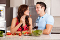 Here taste this beautiful young women cooking dinner and sharing food with her handsome boyfriend Stock Photo