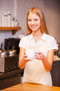 Here you go beautiful young female barista stretching out cup of fresh coffee and smiling while standing at the bar counter Royalty Free Stock Image
