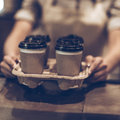 Here you go close up of woman serving coffee to while standing at the wooden bar counter Stock Images