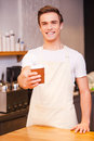 Here you go handsome young male barista stretching out hand with cup of coffee and smiling while leaning at the bar counter Stock Photography