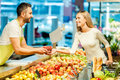 Here you go side view of young cashier giving raspberries to female customer while standing in food store Royalty Free Stock Photo