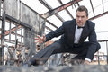 Hero action star handsome tough caucasian man in black tuxedo poses in stunt scene in destroyed warehouse Stock Photography