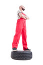 Hero shot low angle of mechanic standing on car wheel in looking up isolated white Stock Photo