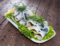 Herring filets on a plate decorated with onions and lattuce Royalty Free Stock Images