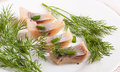 Herring marinaded with fennel on a white plate Stock Photos