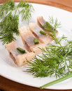 Herring marinaded with fennel on a white plate Royalty Free Stock Photography