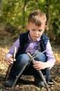 Het leuke little boy spelen met stokken bij het hout Royalty-vrije Stock Fotografie