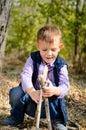 Het leuke little boy spelen met stokken bij het hout Stock Afbeeldingen