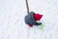 Het meisje met rode hoedenschop graaft sneeuw Stock Foto