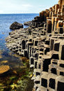 The hexagonal basalt slabs of giants causeway dipping into the sea antrim coastline northern ireland is Royalty Free Stock Photography