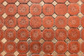 Hexagonal floor tiles old victorian floral pattern showing wear Stock Image
