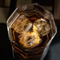 Hexagonal glass of whiskey with three cubes of real ice top view