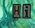 Hi spelled with letterpress blocks on green Royalty Free Stock Photo