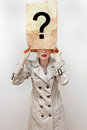 Hidden identity young woman in trench coat hides her with face covered under paper bag with question mark Royalty Free Stock Photography